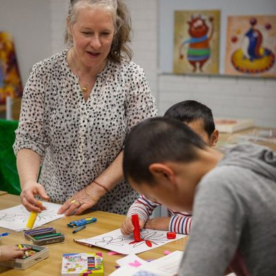 teacher assisting children in colouring class