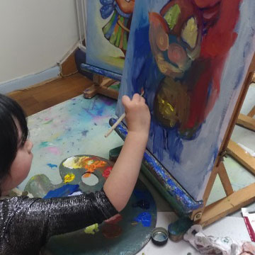 child using a brush for oil painting