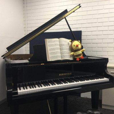 a bernstein piano with note and bumblebee arts centre doll
