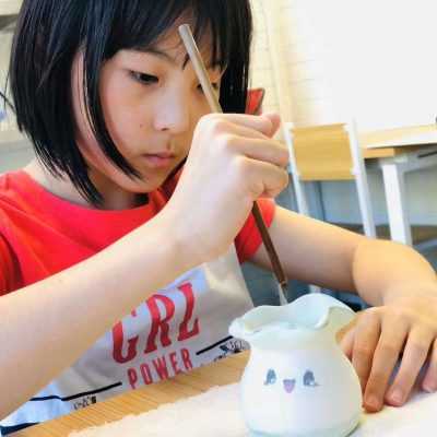 child colouring a pottery
