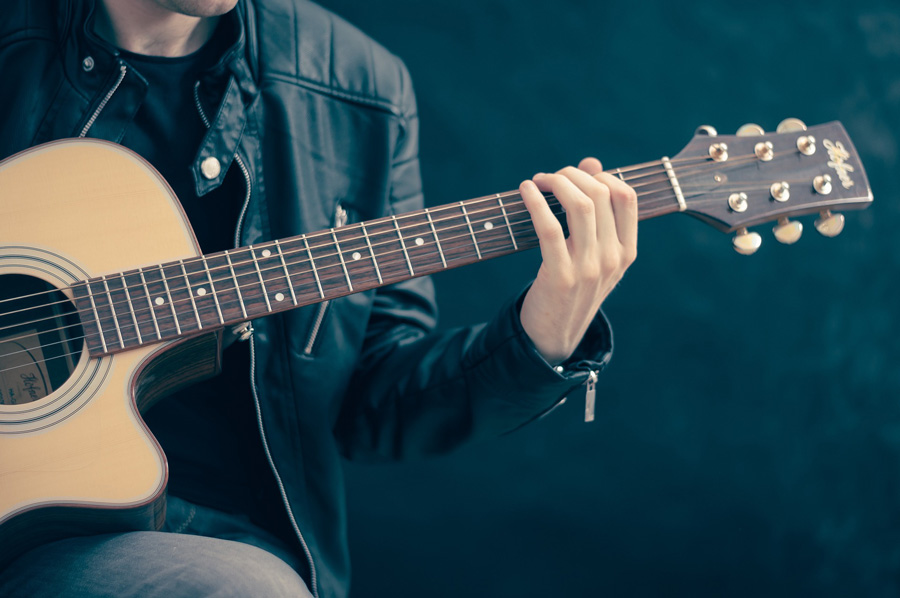 close up of a man playing a guitar