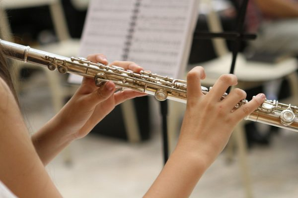 close up of hands playing a flute in an orchestra