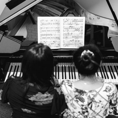 teacher and student are practicing piano